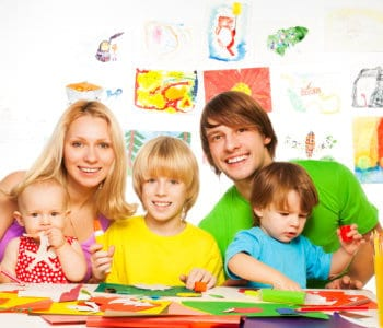 two parents and three kids little boys and baby girl crafting with paper glue and scissors
